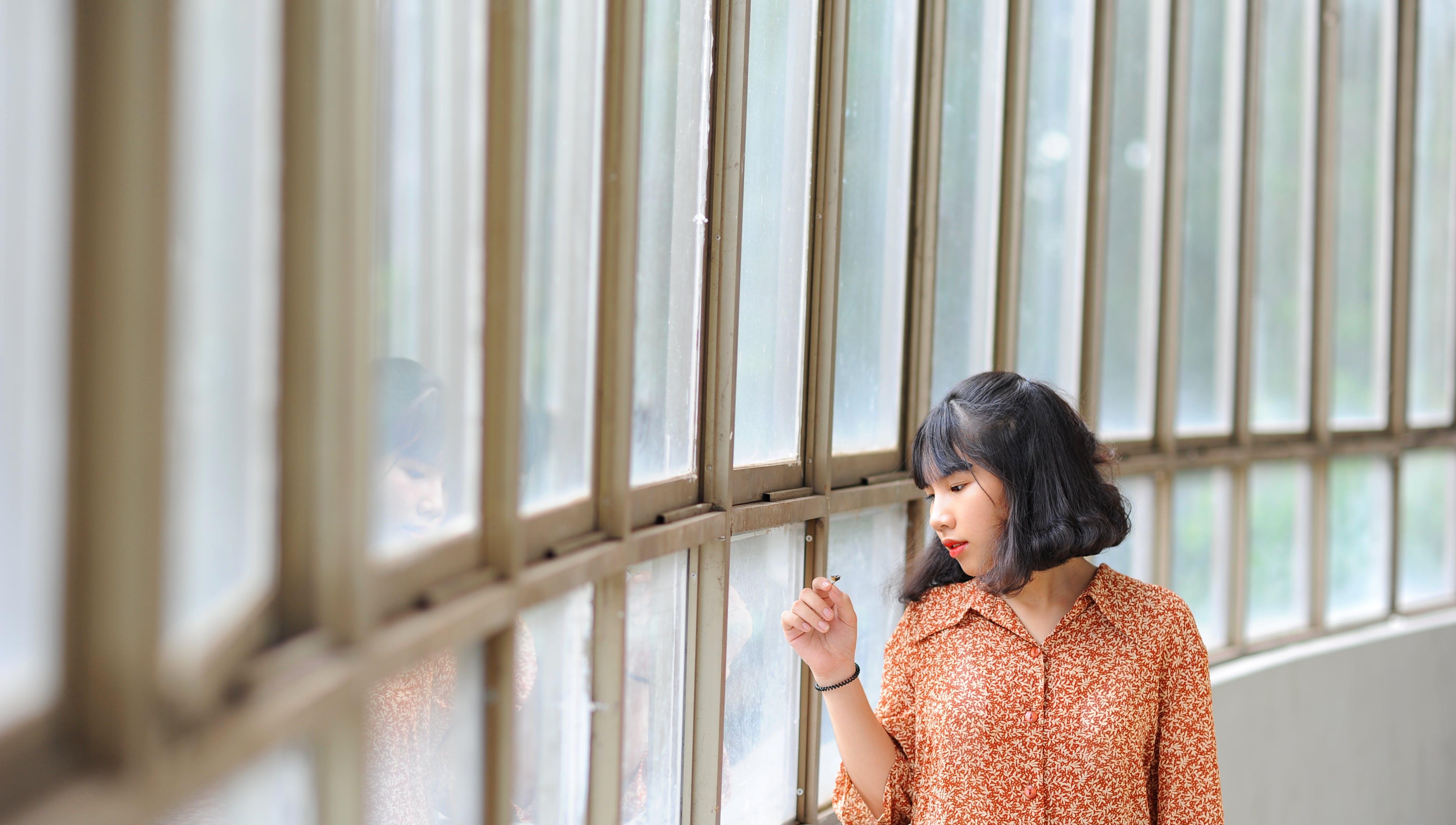 Woman Leaning Beside Glass Window