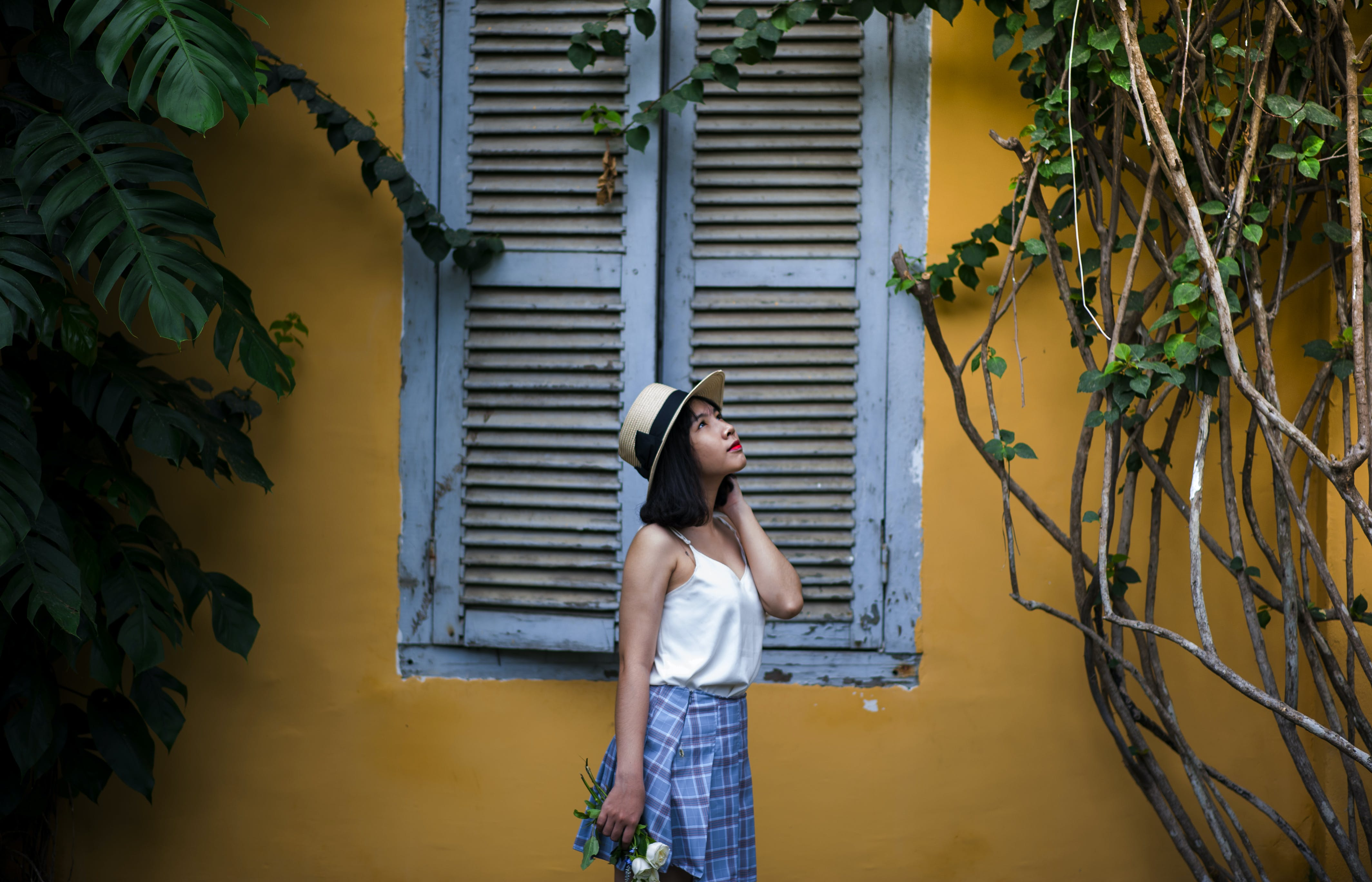 Woman Standing Near Louvered Window Holding White Roses