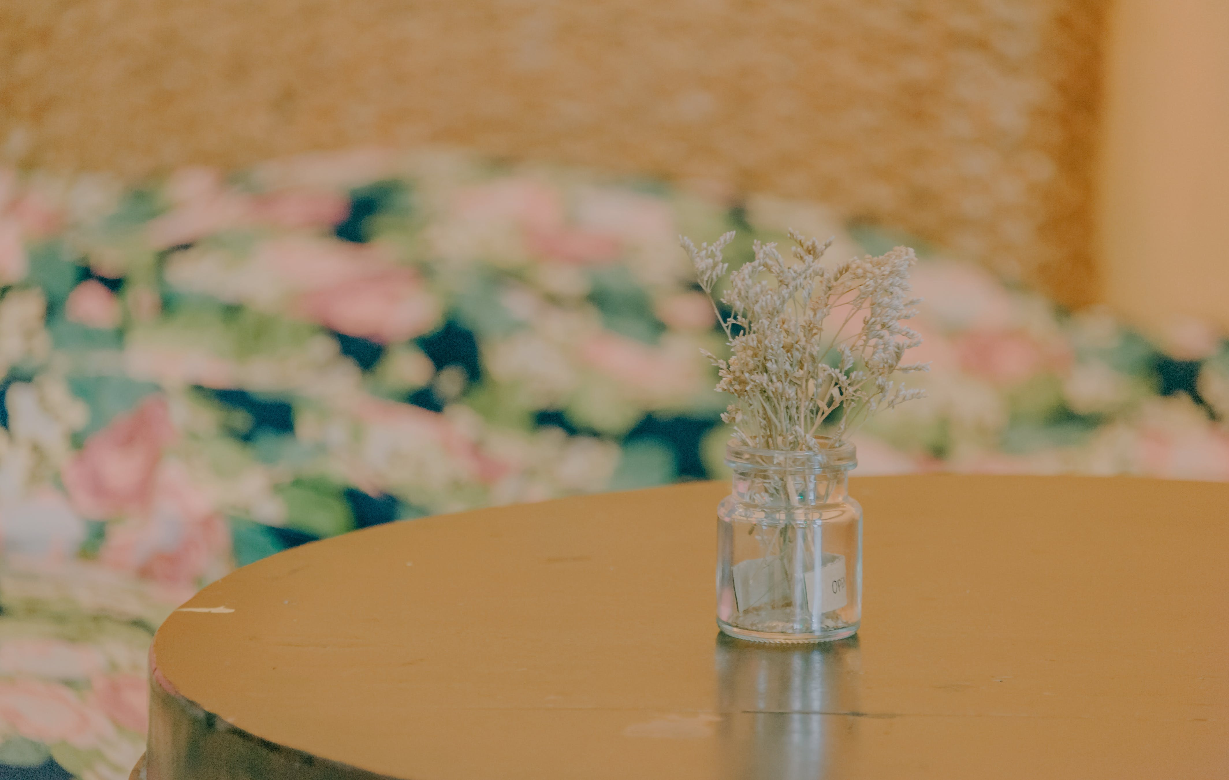 Flowers In Glass Bottle On Table