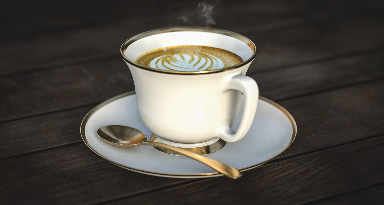 White Ceramic Mug Beside Gold Spoon