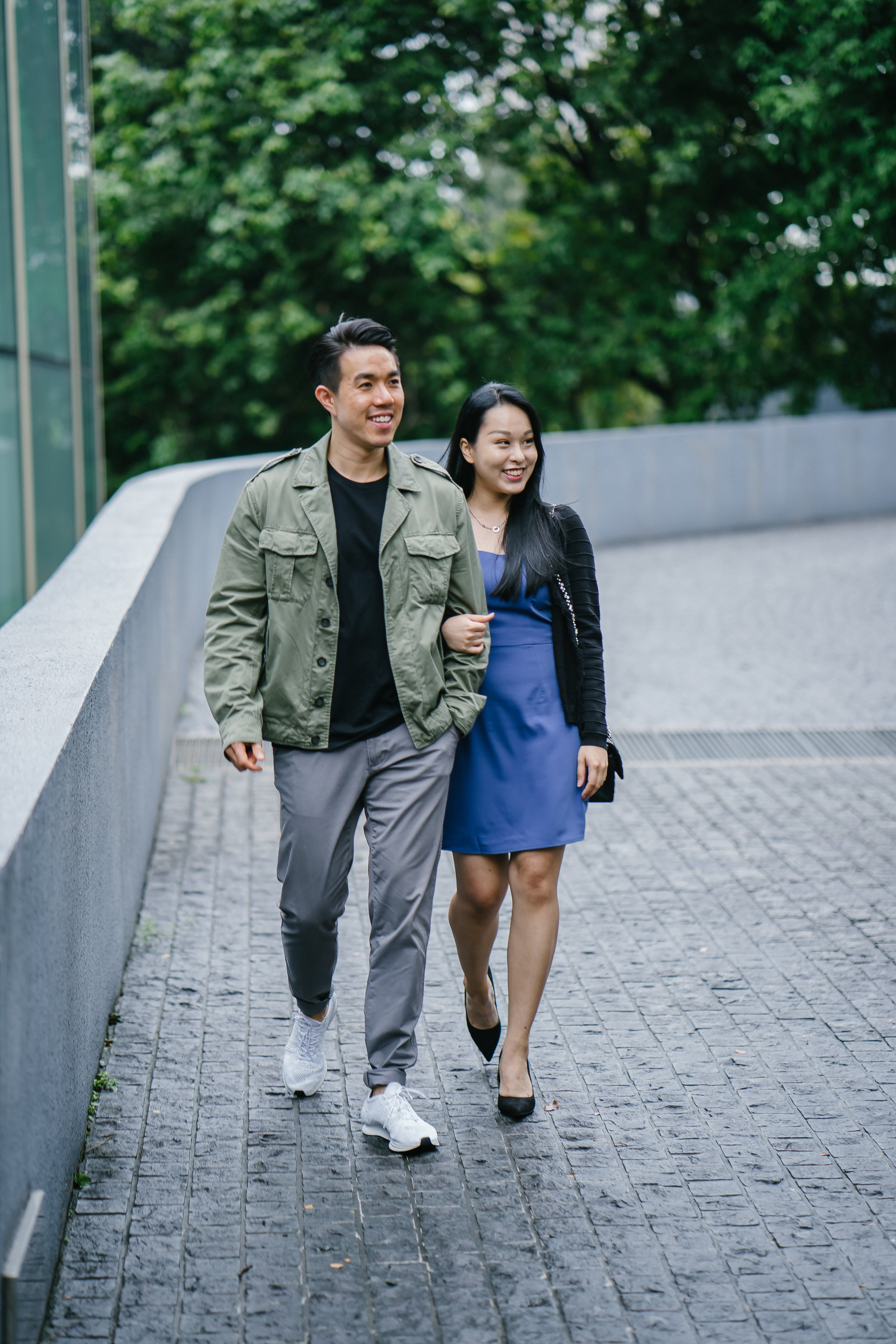 Man and Woman Walking Beside A Building