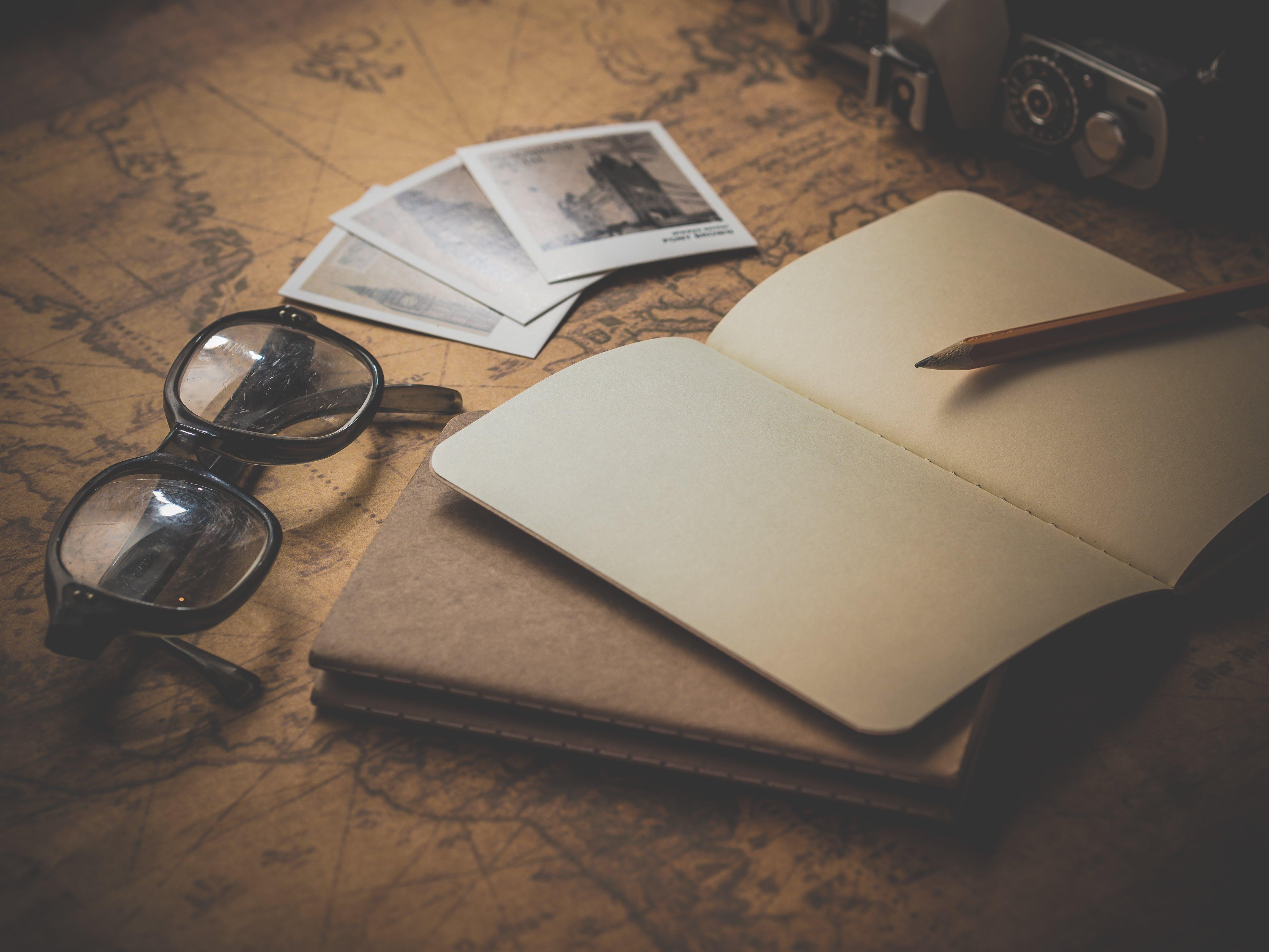 Black Frame Eyeglasses Beside Open Book