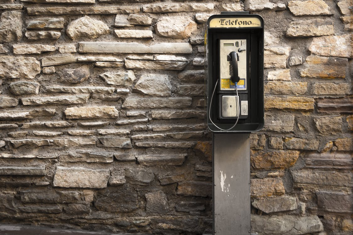 Gray and Black Telephone Booth Standing Near Gray Stone Wall at Daytime