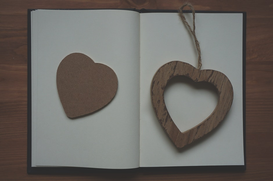 Brown Wooden Heart Shape Pendant on White Book