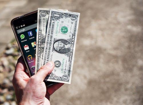 Základová fotografie zdarma na téma americké dolary, chytrý telefon, dolary, hotovost