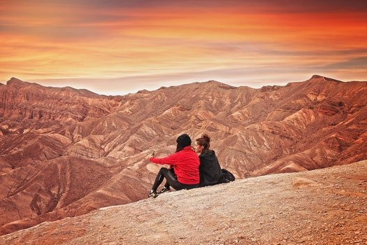 2 Woman Seating on the Mountain Cliff during Golden Hour