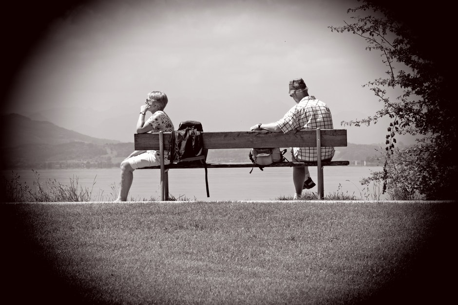 Man Sitting on Other Edge of Bench Parallel to Woman With Bags in Between Them