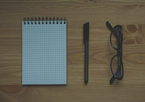 ahşap, gözlük, masa, mürekkepli kalem içeren Ücretsiz stok fotoğraf