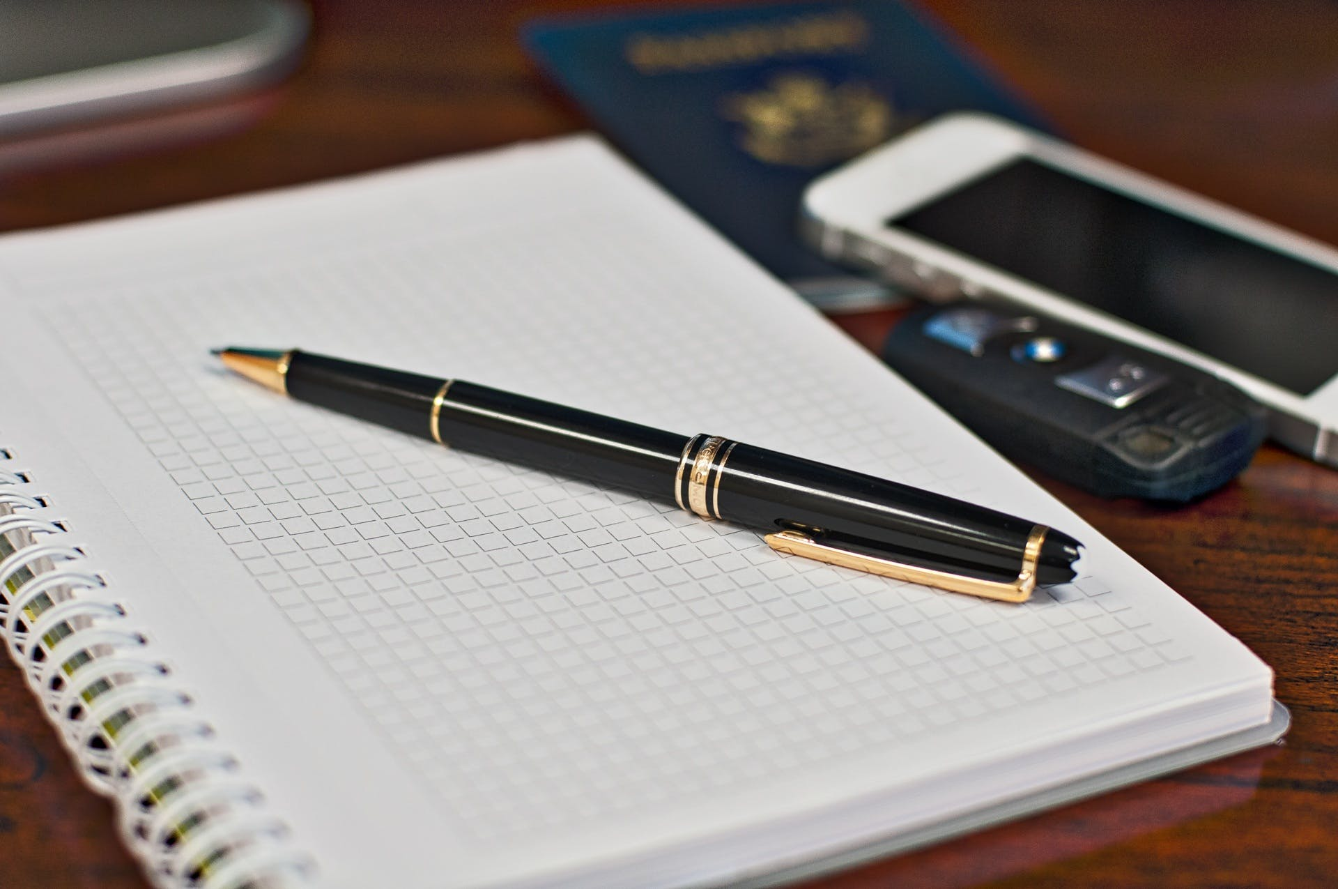 Black and Gold Twist Pen Near White Smartphone
