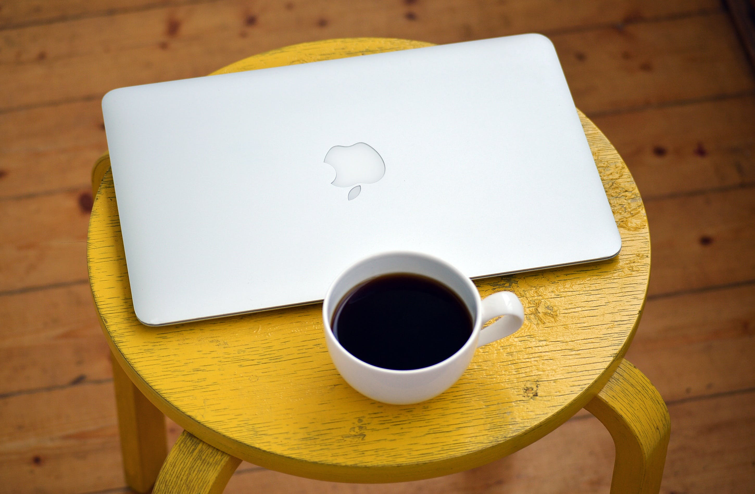 Silver Macbook Beside White Cup