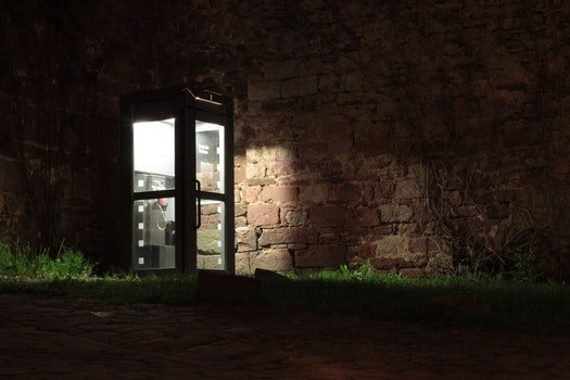 Telephone Booth Beside Brown Wall during Nighttime
