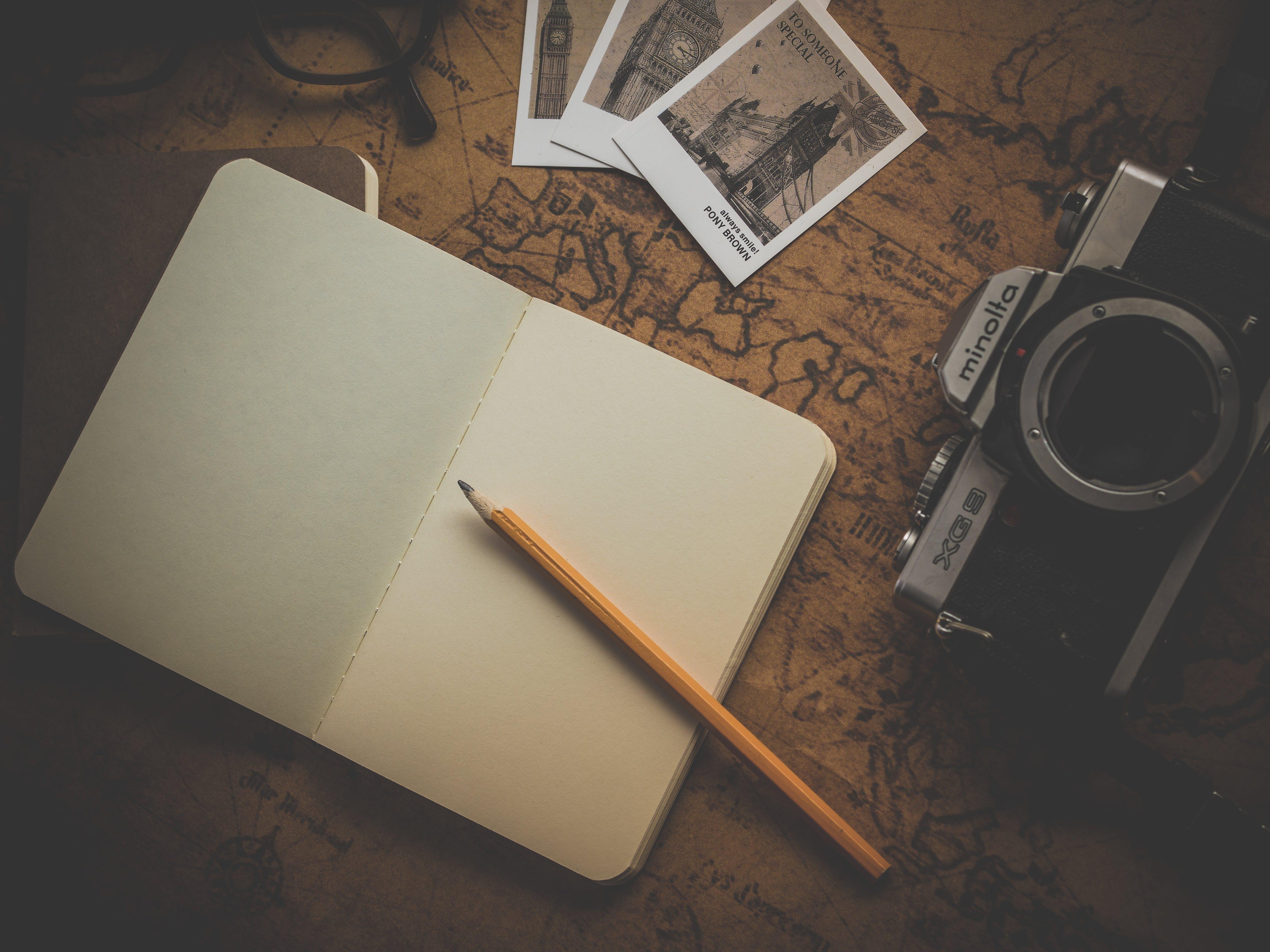 Yellow Pencil on White Book Near Camera