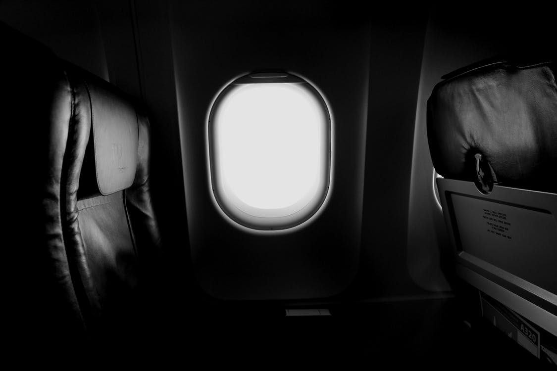 Grayscale of Airplane Window and Chair