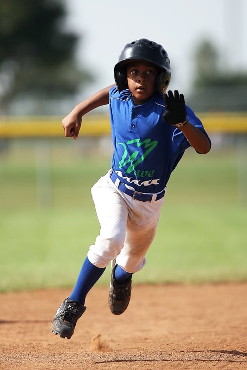 Boy in Blue and White Baseball Jersey Running on Brown Soil Field during Daytime