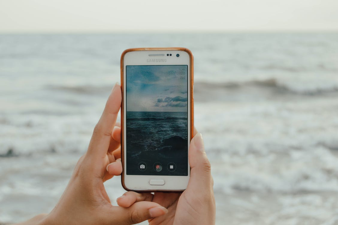 Person Holding Smartphone Capturing Ocean Waves