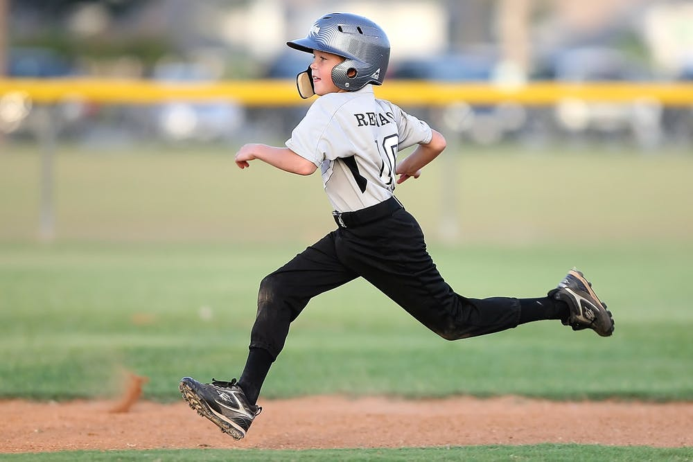 A young baseball player running in the baseball field.   Photo: Pexels