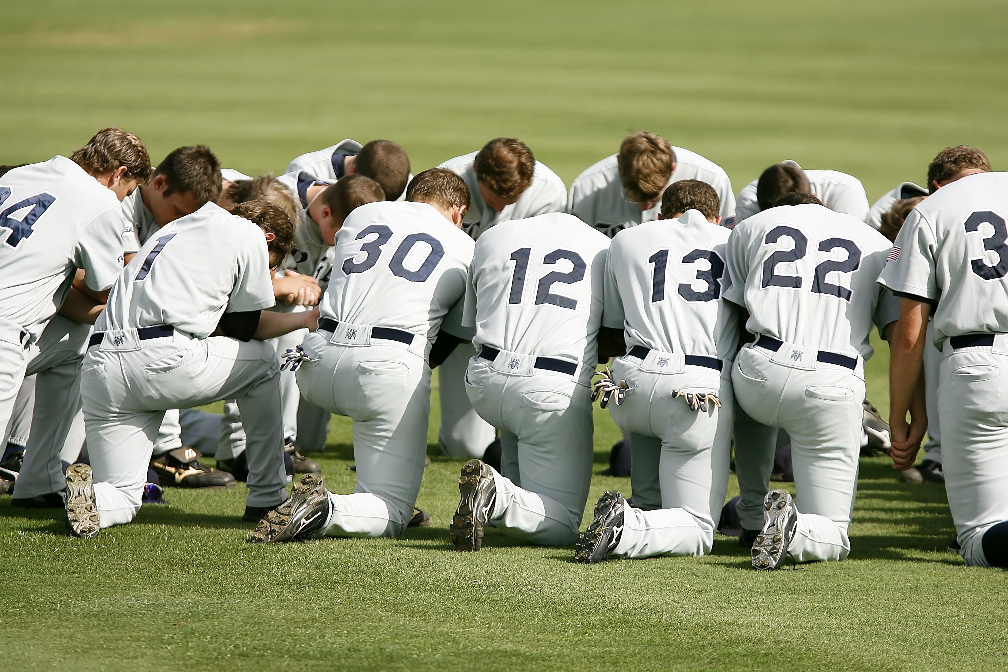 Baseball Player Kneeling on Grass Field during Daytime