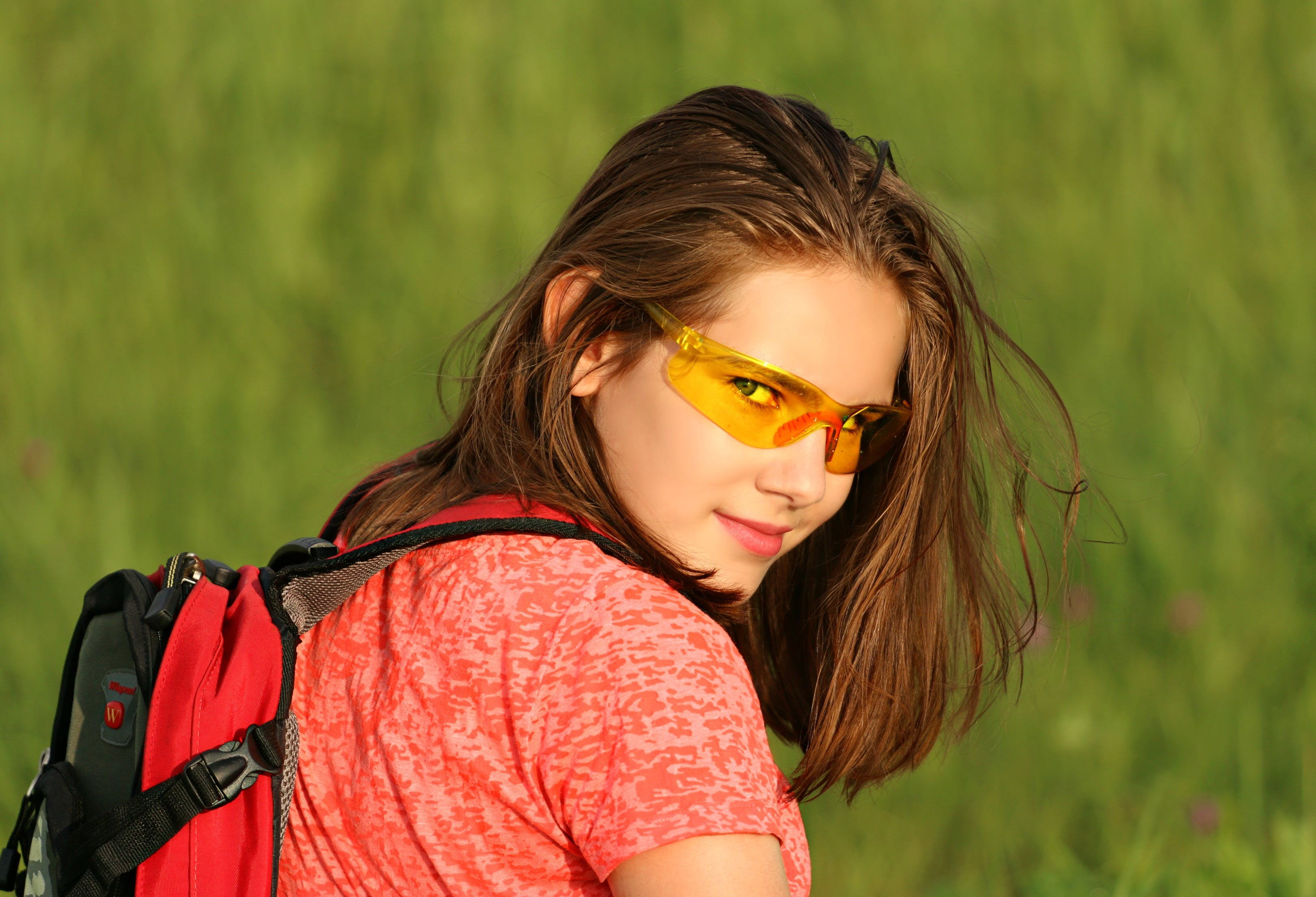 Woman in Red Shirt Wearing Backpack Surrounded by Green Grass Field