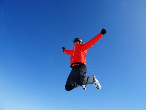 Man in Orange Zip Jacket and Black Pants Jumping Under Blue Sunny Sky