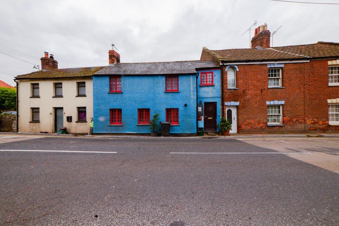 Бесплатное стоковое фото с дорога, облачное небо, разноцветные дома