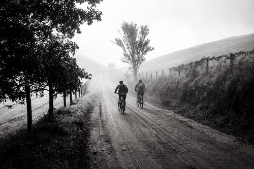 Grayscale Photography of Two Person Biking