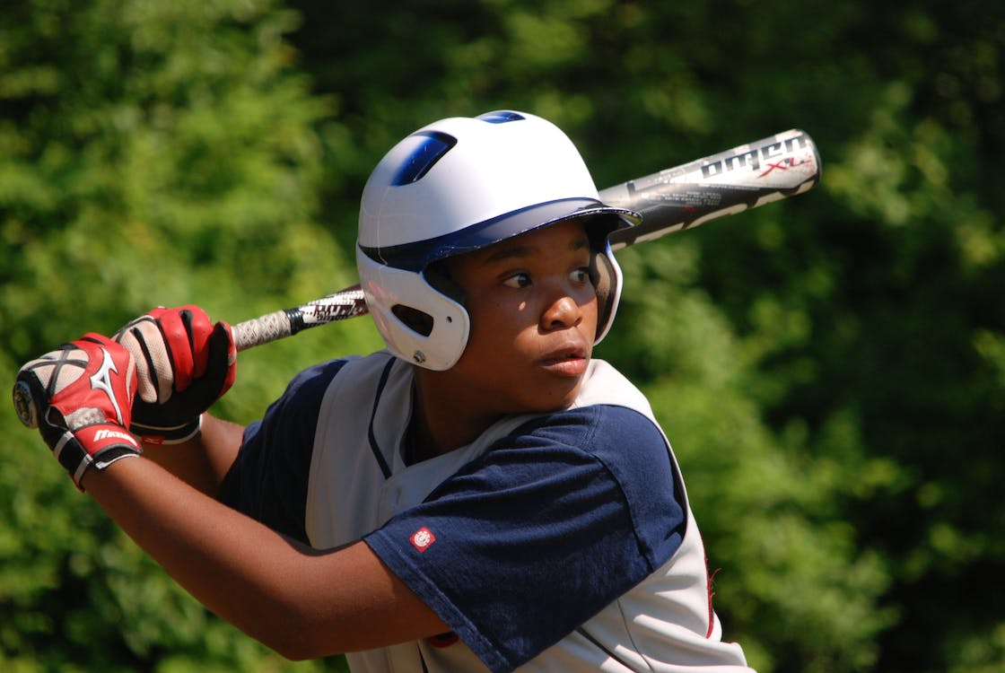 Boy in Baseball Suit Near Green Tree during Daytime