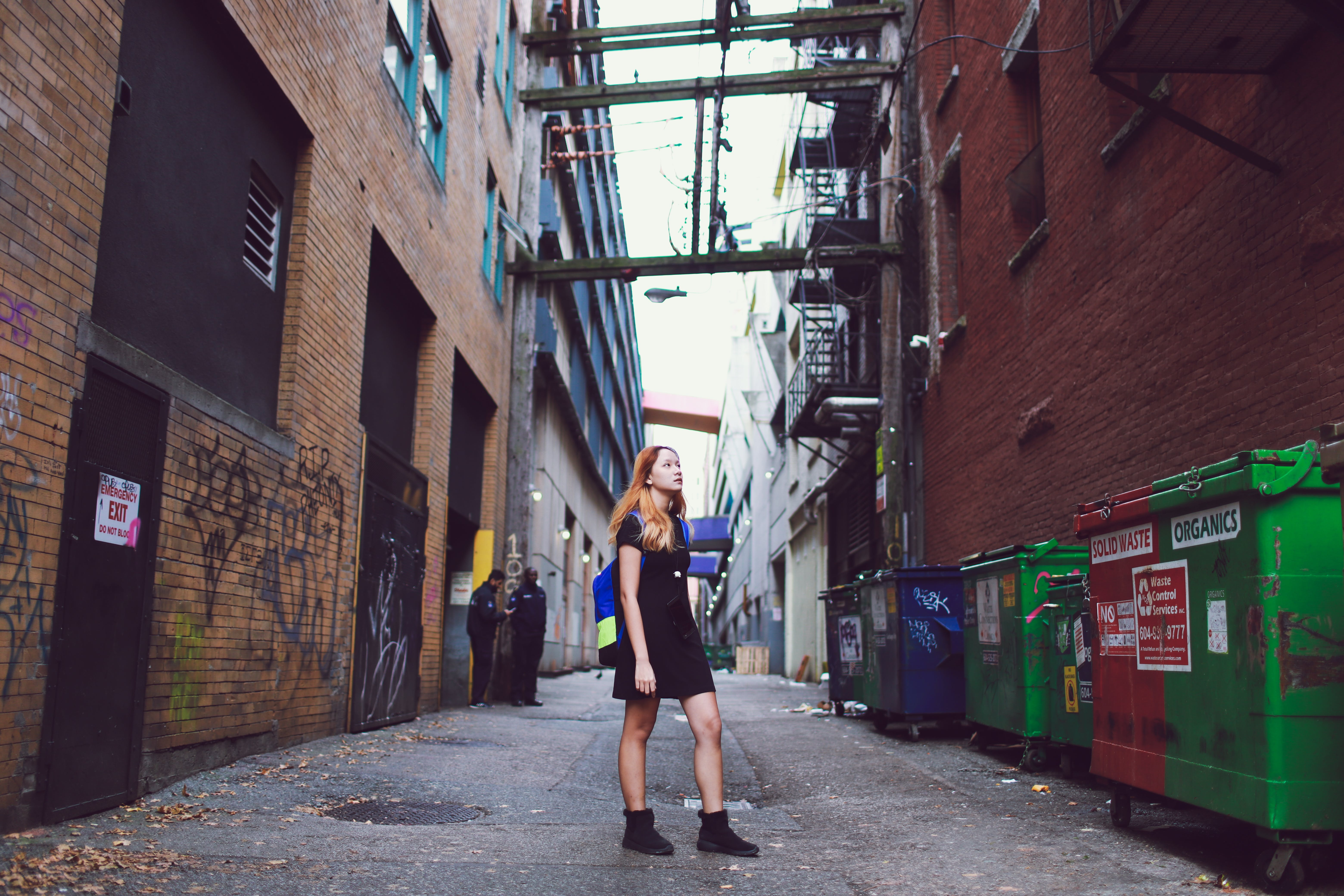 Photo of a Woman Standing Between Buildings