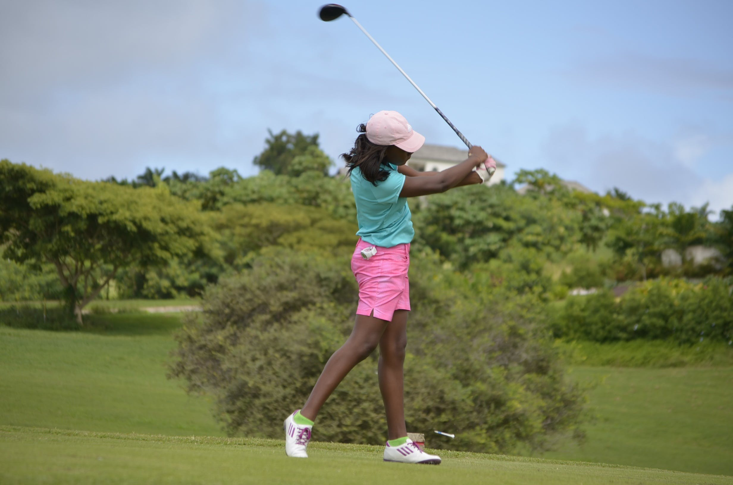 Woman in Green Polo Shirt and Pink Shorts Playing Golf Under Grey and Blue Skies during Daytime