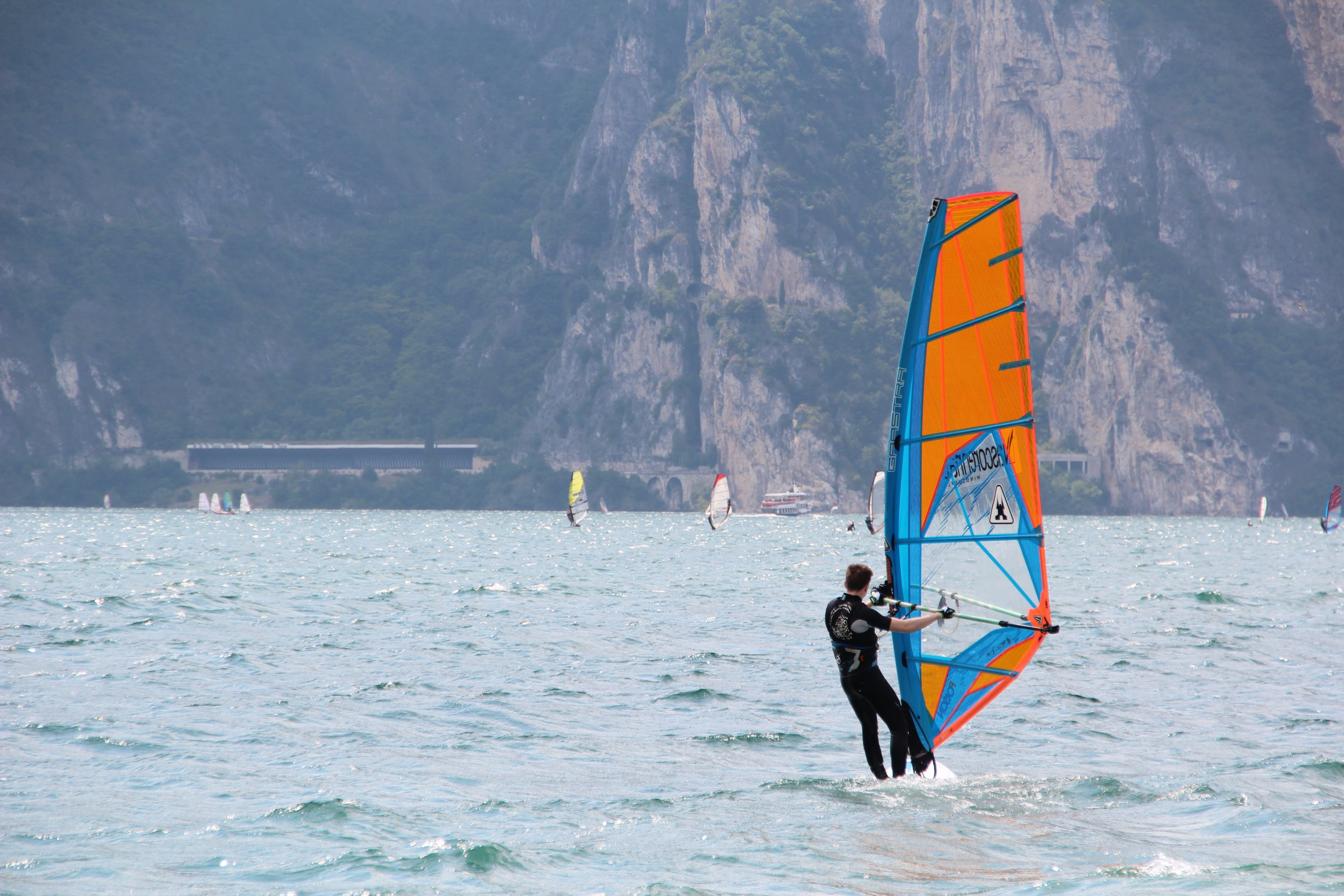 Man in Black Wetsuit Standing on Orange and Blue Sailboat during Daytime