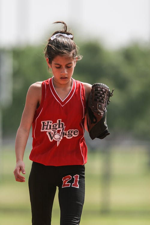 девушка в красно черной униформе для софтбола идет