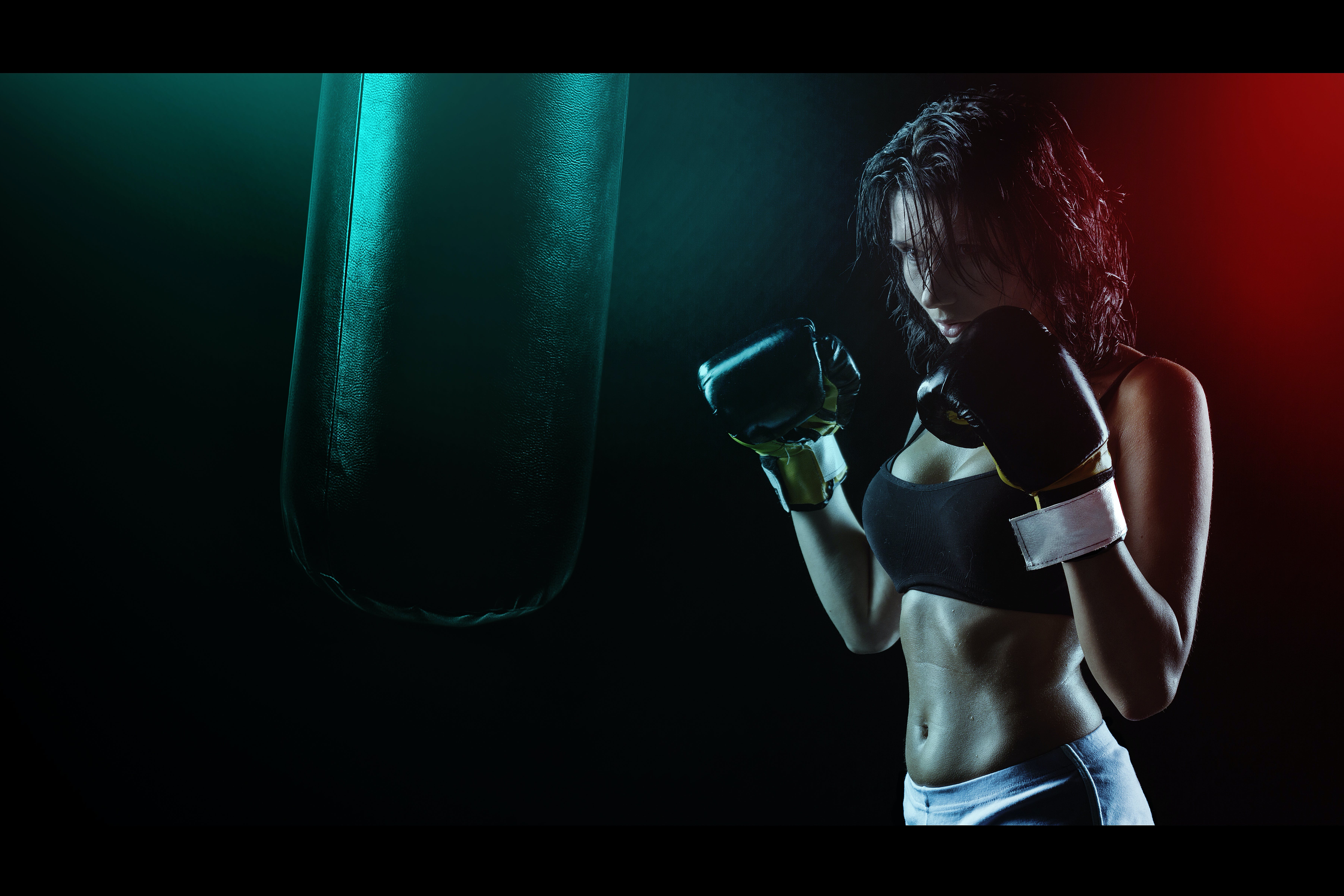 Woman in Boxing Gloves With Sports Bra Posing Boxing Style in Front of Punching Bag