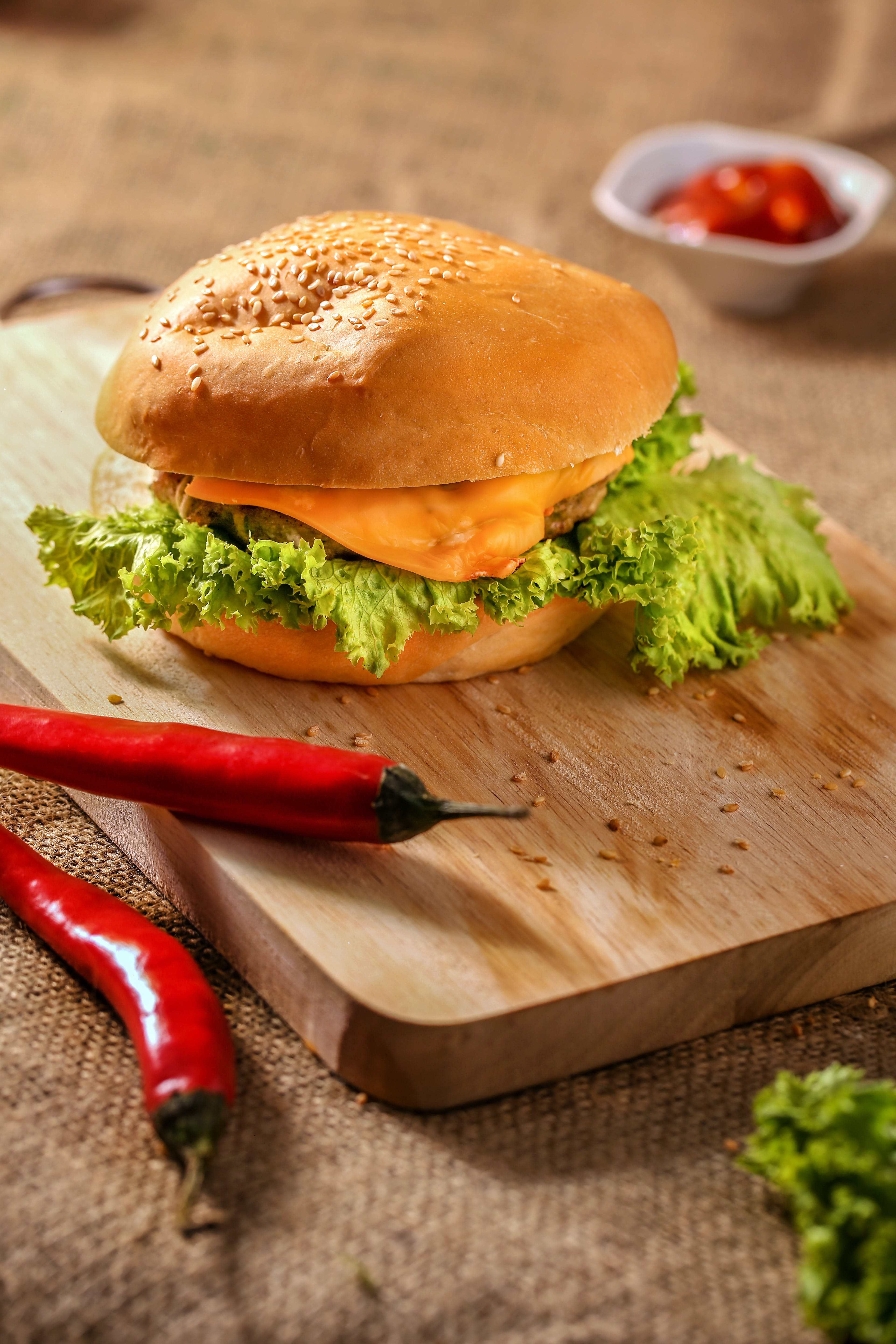 Burger on Top of Wooden Board Near Two Red Chili
