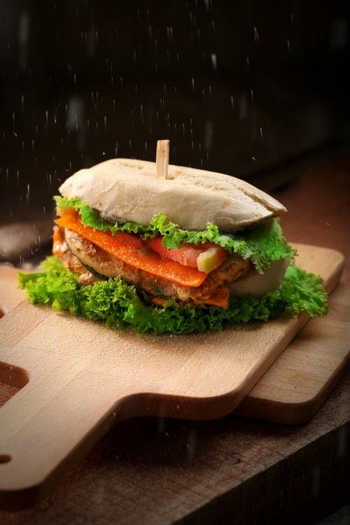 Burger on Top of Brown Chopping Board