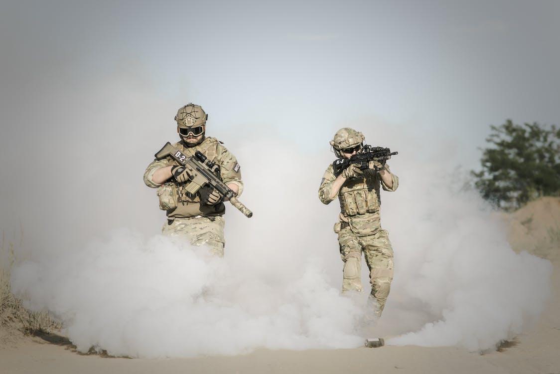 Men Holding Rifle While Walking Through Smoke Grenade
