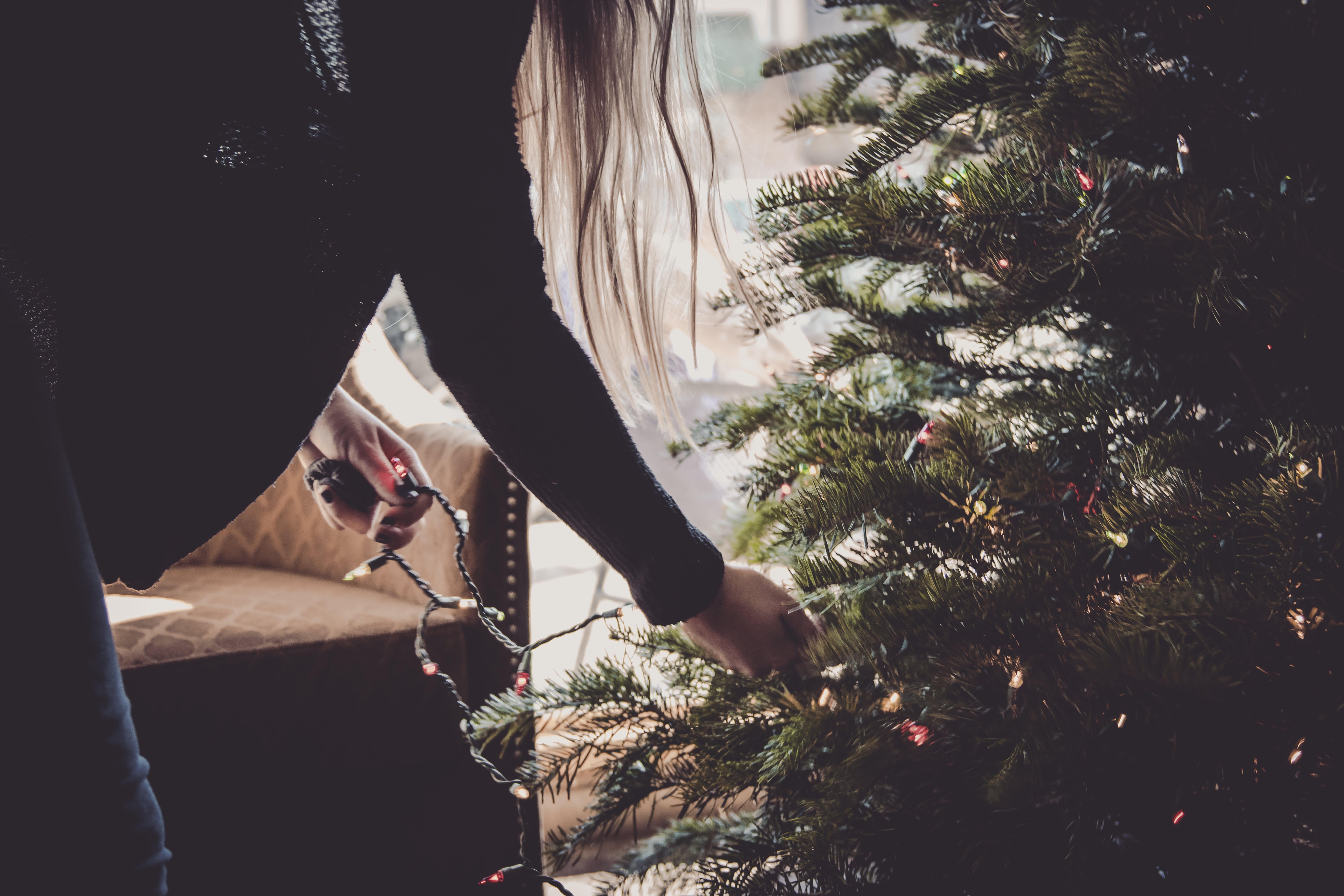 Woman Putting String Lights on Christmas Tree