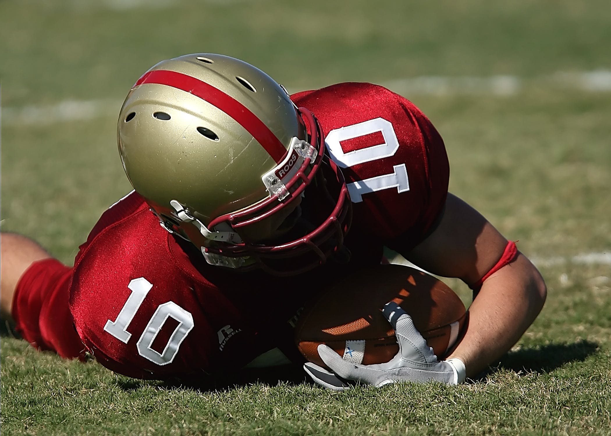 Man in Red White Football Jersey and Grey Red Helmet Holding Football and Lying on Green Grass Field