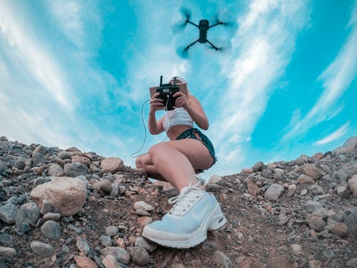 Photo Of Woman Playing With Drone Quadcopter Under Blue Sky
