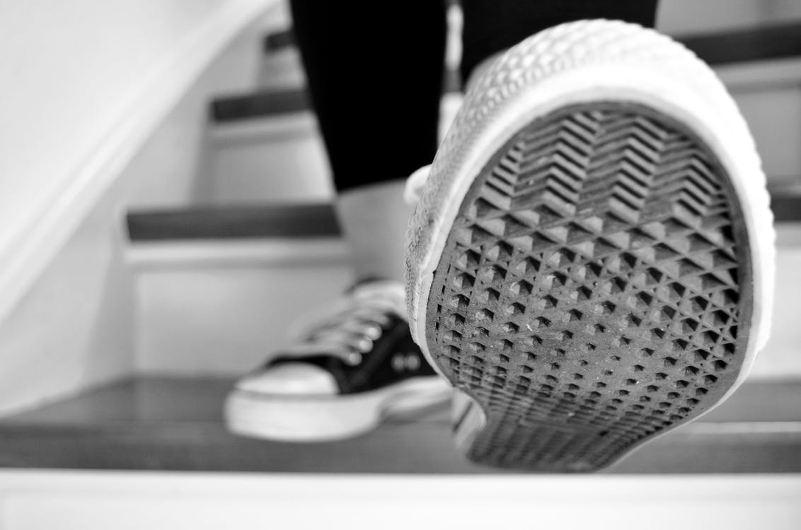 Grayscale Photo of Shoes and Stairs