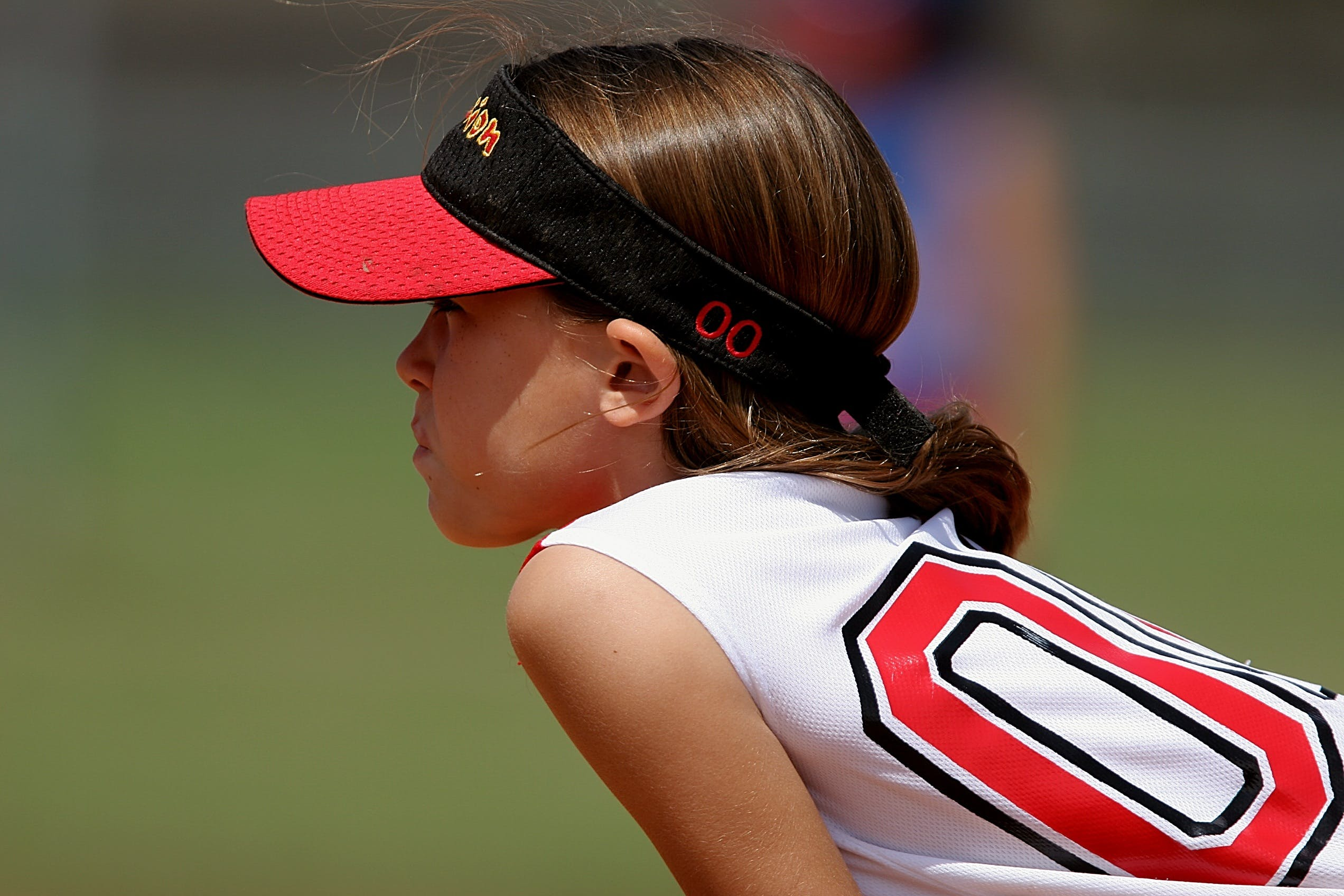 Girl Wearing Red and Black Sun Visor and White and Red Jersey Top