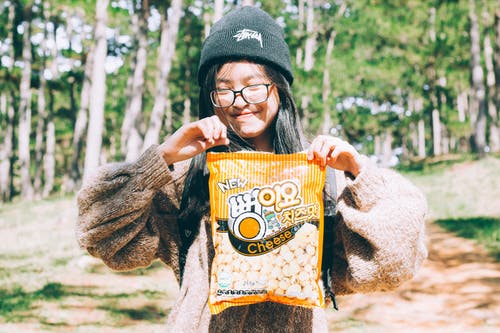 Selective Focus Photography of Girl Holding Popcorn Pack