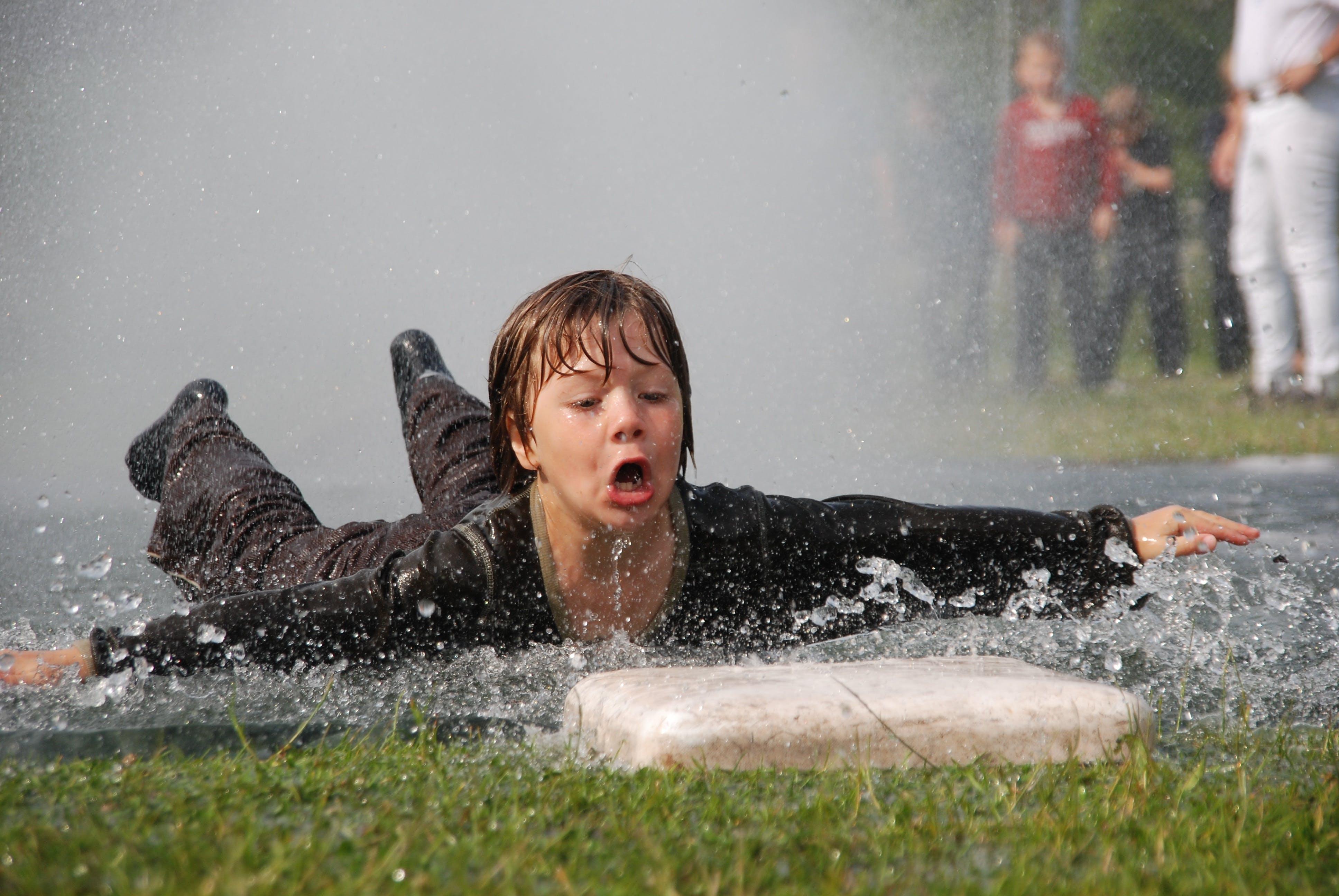 Boy Wearing Black Long Sleeve Shirt Sliding Near Green Grass
