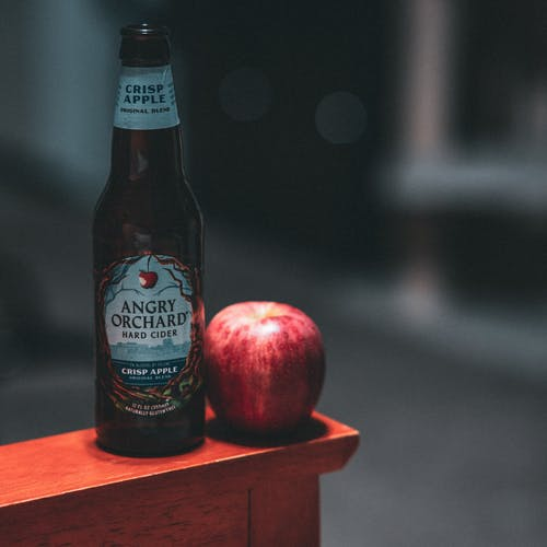 Angry Orchard Hard Cider Bottle Beside Red Apple Fruit