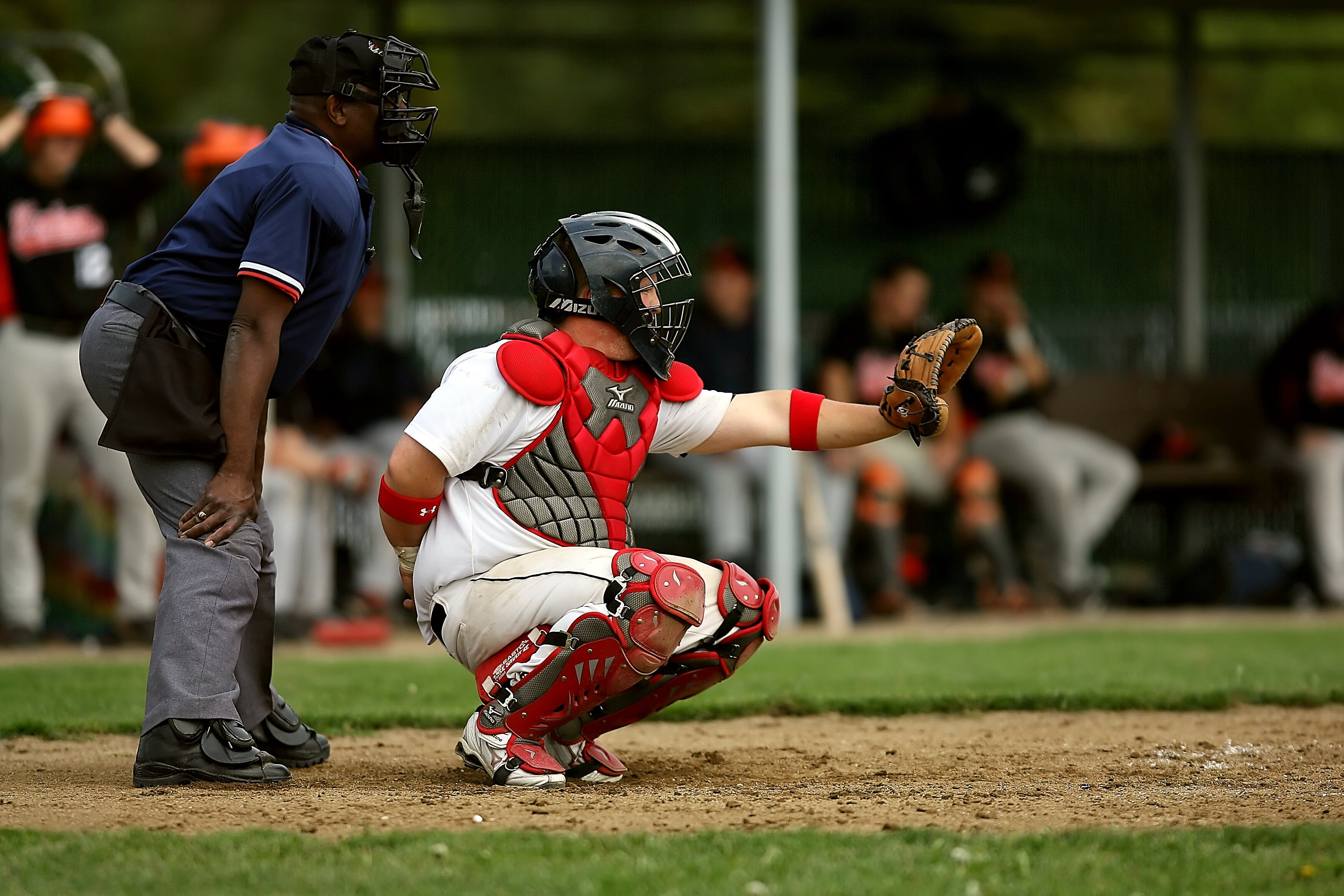 White and Red Baseball Player With Black Face Helmet and Brown Leather Mitts