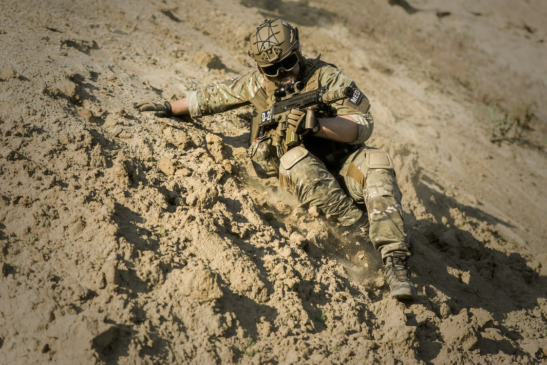 Soldier Sliding Downhill Holding Rifle during Daytime