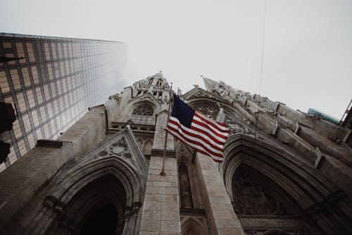 Low Angle Photography of Waving Usa Flag on Brown Concrete Cathedral