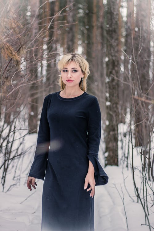 Женщина, стоящая на заснеженной земле в окружении деревьев