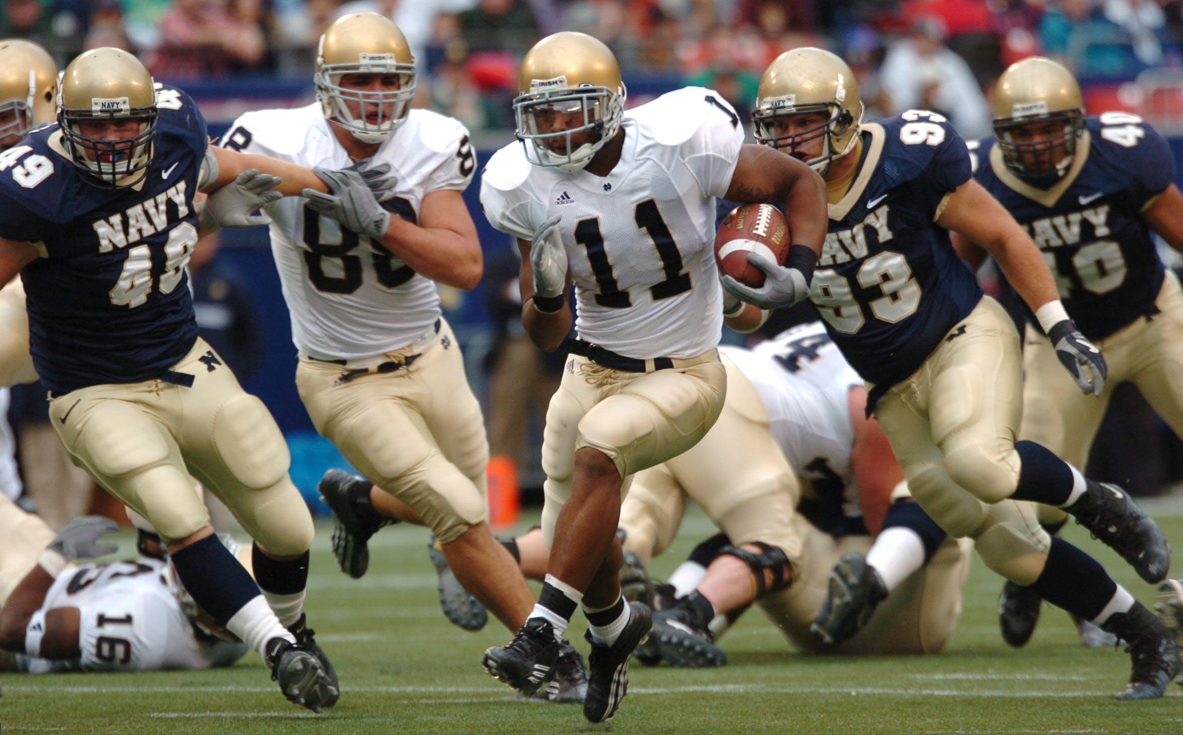 Group of Male Football Players Running on Field during Day
