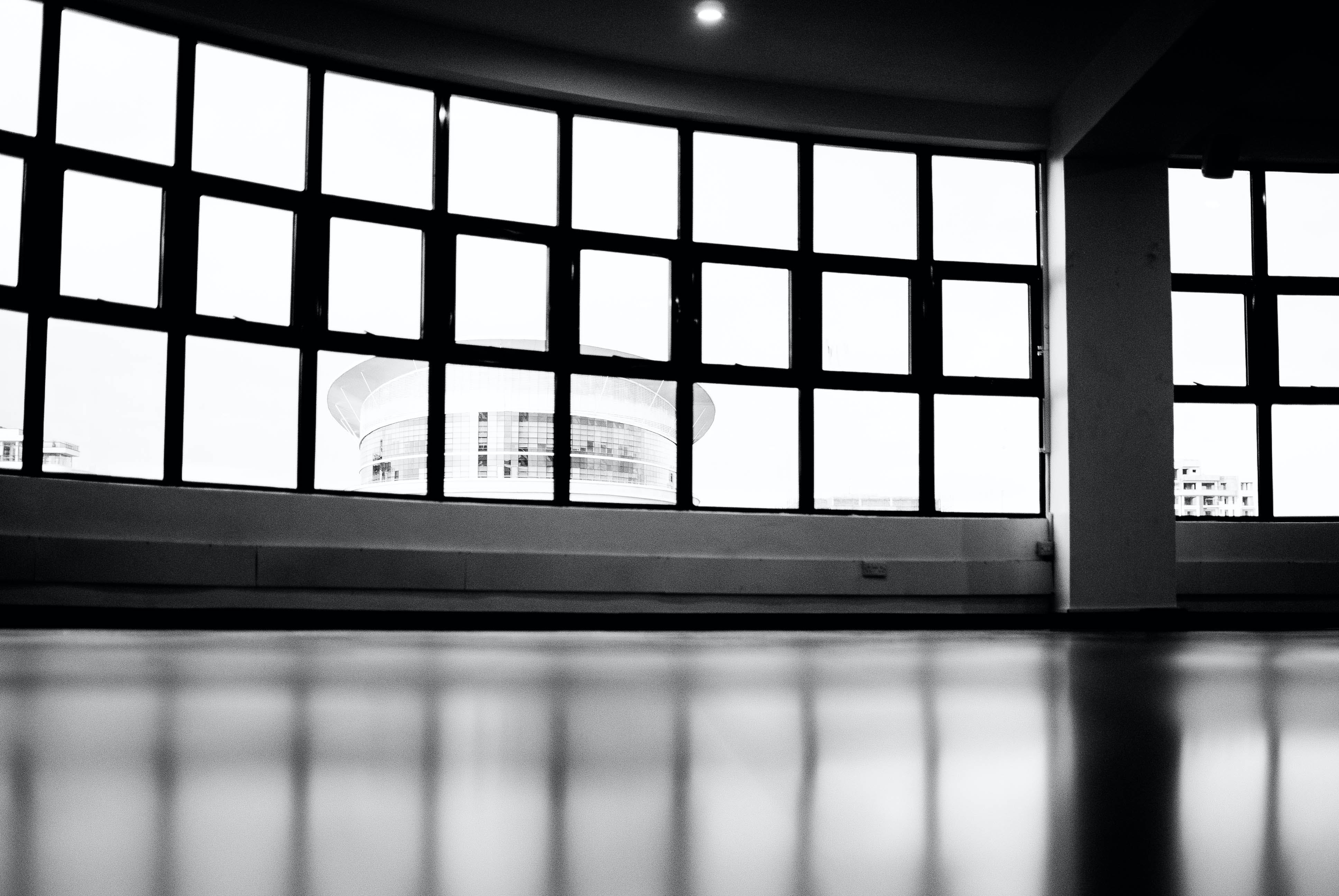 Low-angle and Grayscale Photography of Glass Pane Windows Overlooking Round Building