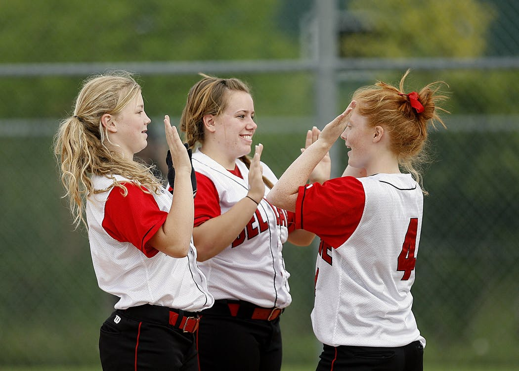 Girls in red and white jerseys playing hand games.