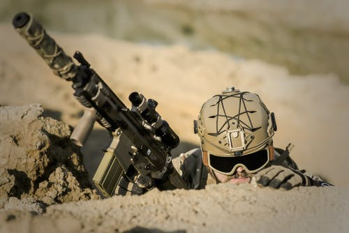 Soldato Che Indossa Il Casco Marrone Che Tiene Il Fucile D'assalto Durante Il Giorno